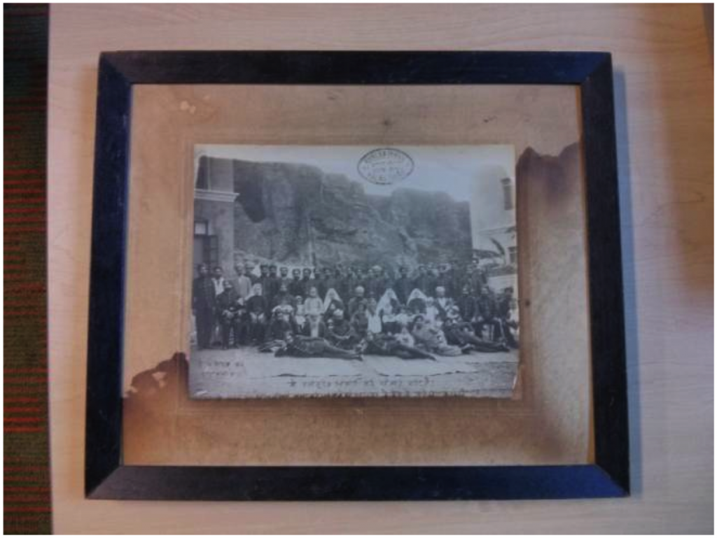 The photograph was removed from the frame as there was water damage and was unaesthetic for digitization (front of frame). Photo by Anne Lama.