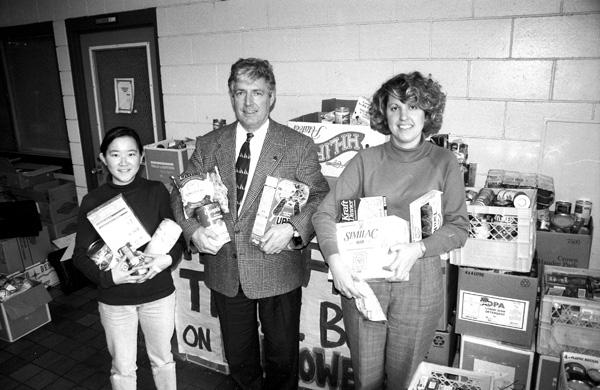Lica Chui, Charles Slonecker and Carole Forsythe with food collected by U.B.C. students during the Trick or Treat for the Food Bank on Halloween, 1995